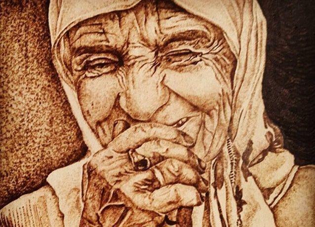 بالصور : فنان يرسم لوحات فنية عن طريق حرق الخشب