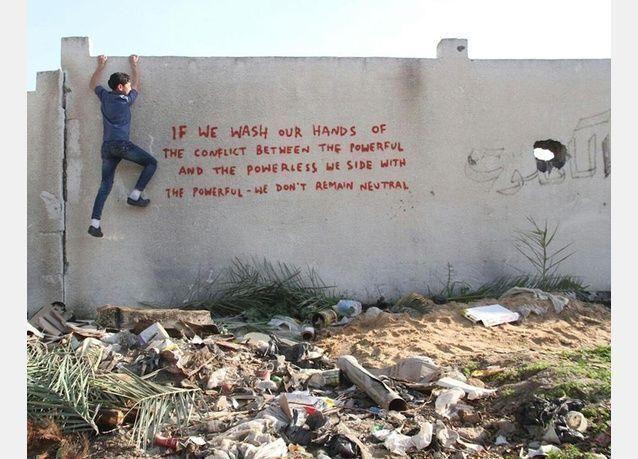 البريطاني بانكساي يرسم الجرافيتي على حُطام منازل غزة