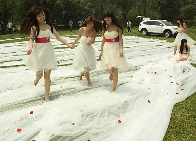 بالصور: 20 فتاة لحمل طرحة فستان زفاف بطول 520 متراً