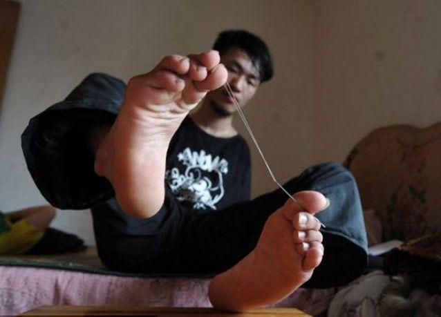 بالصور: طالب صيني متفوق فقد ذراعيه ويمارس حياته معتمداً على قدميه