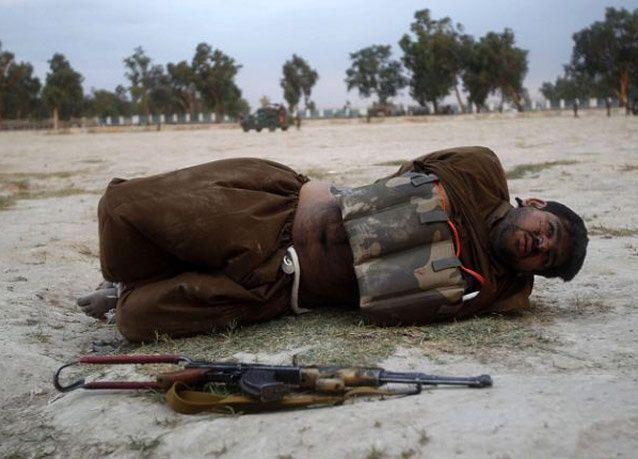بالصور: جندي أفغاني يفكك حزاماً ناسفاً بعد تكبيل الإرهابي