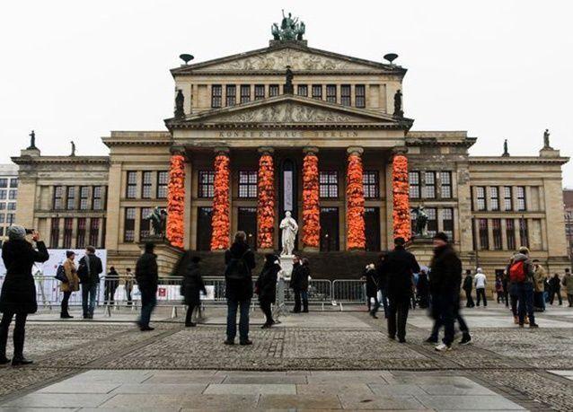 """بالصور : فنان صيني يزين أعمدة برلين بـ """"سترات نجاة"""" اللاجئين"""