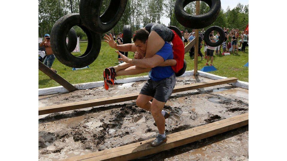 بالصور : مسابقة تحدي الأزواج بحمل الزوجات على الأكتاف في روسيا