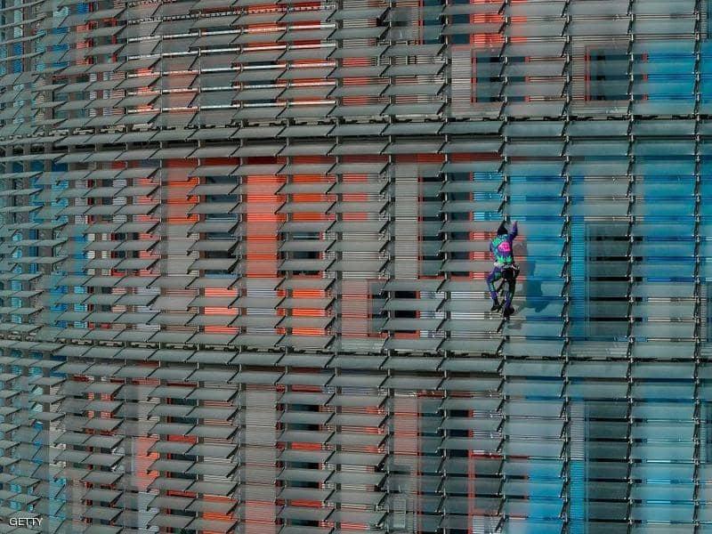 شاهد.. الرجل العنكبوت يتسلق برجاً في برشلونة للتوعية بـ كورونا