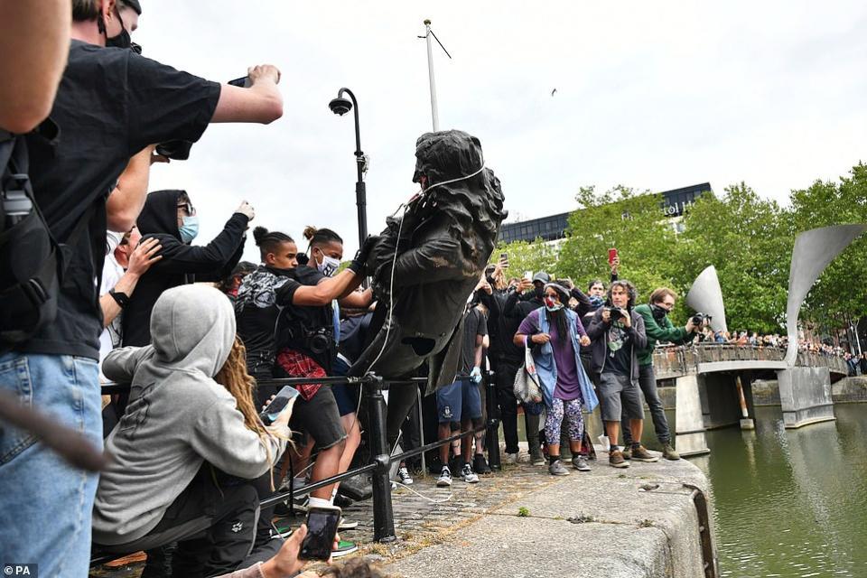 بالصور، اسقاط وتشويه تماثيل رموز العنصرية في بريطانيا